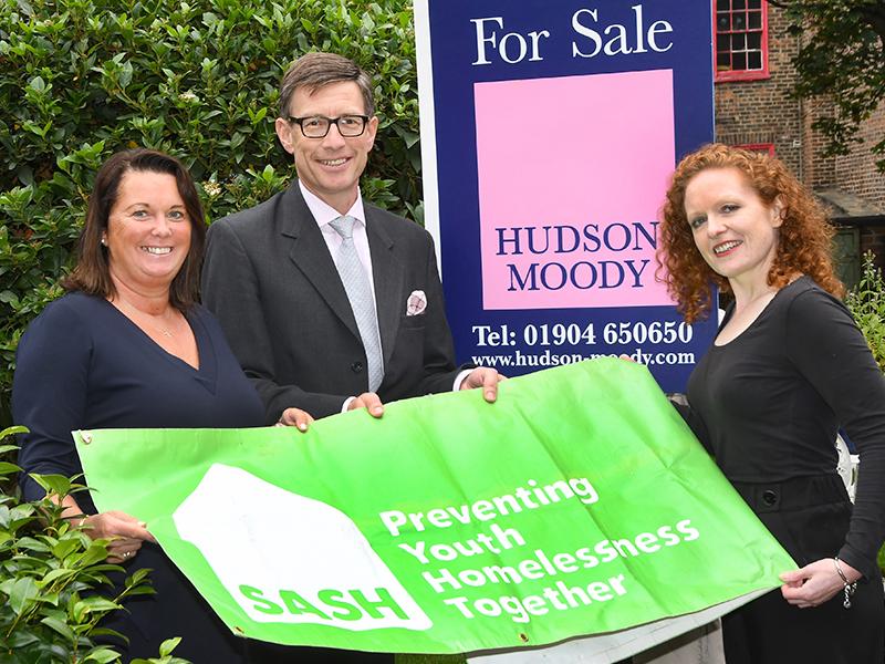 Ben and Tarnia Hudson stood holding SASH banner with Ruth Fawcett, SASH