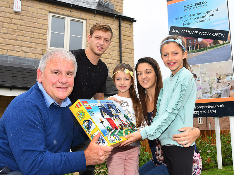 Head of Sales David Harrison with new home buyers and box of LEGO