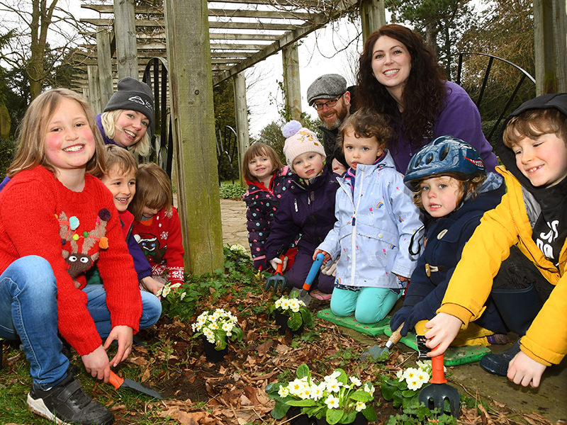 Marketing Managers Helen Fletcher and Michelle McCarthy with children planting flowers