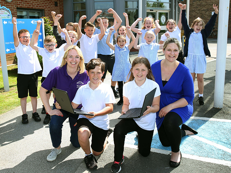 Marketing Manager Helen Fletcher with Hob Moor Primary School students and laptops